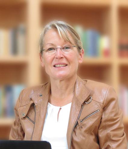 Eva Schwarz mit Laptop vor Bücherregal